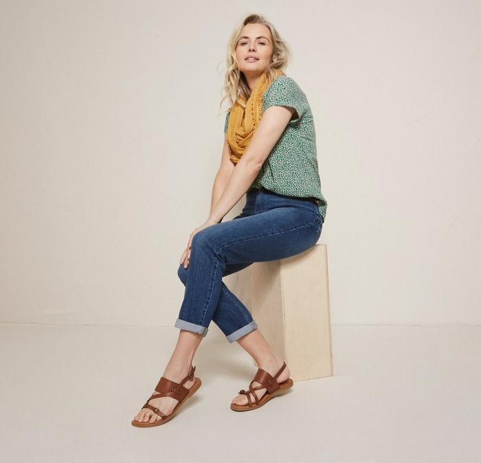 Female model wearing a green ditsy print top, jeans and brown cross over ankle strap sandals.