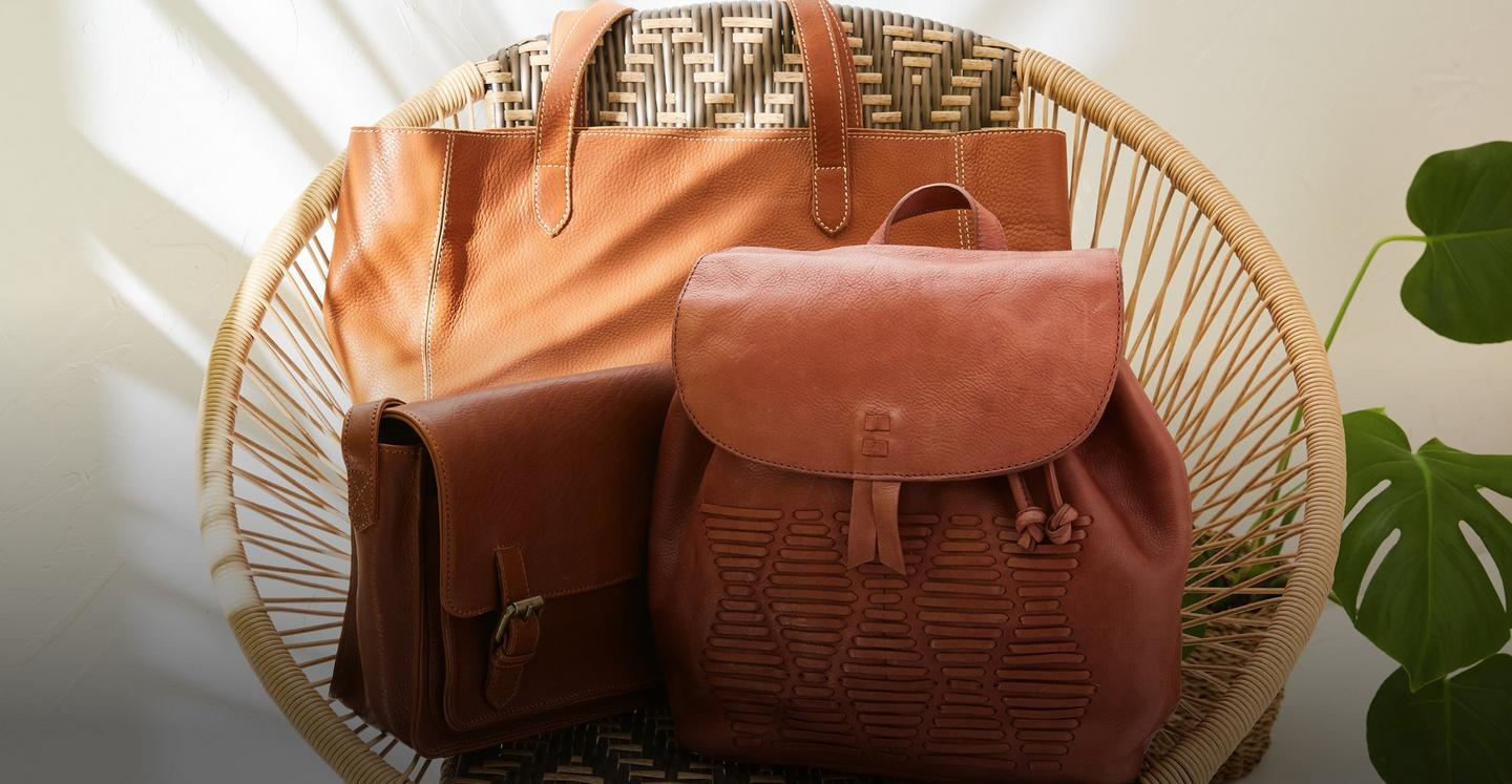 A selection of tan leather bags, satchels and a rucksack displayed on a wicker chair.
