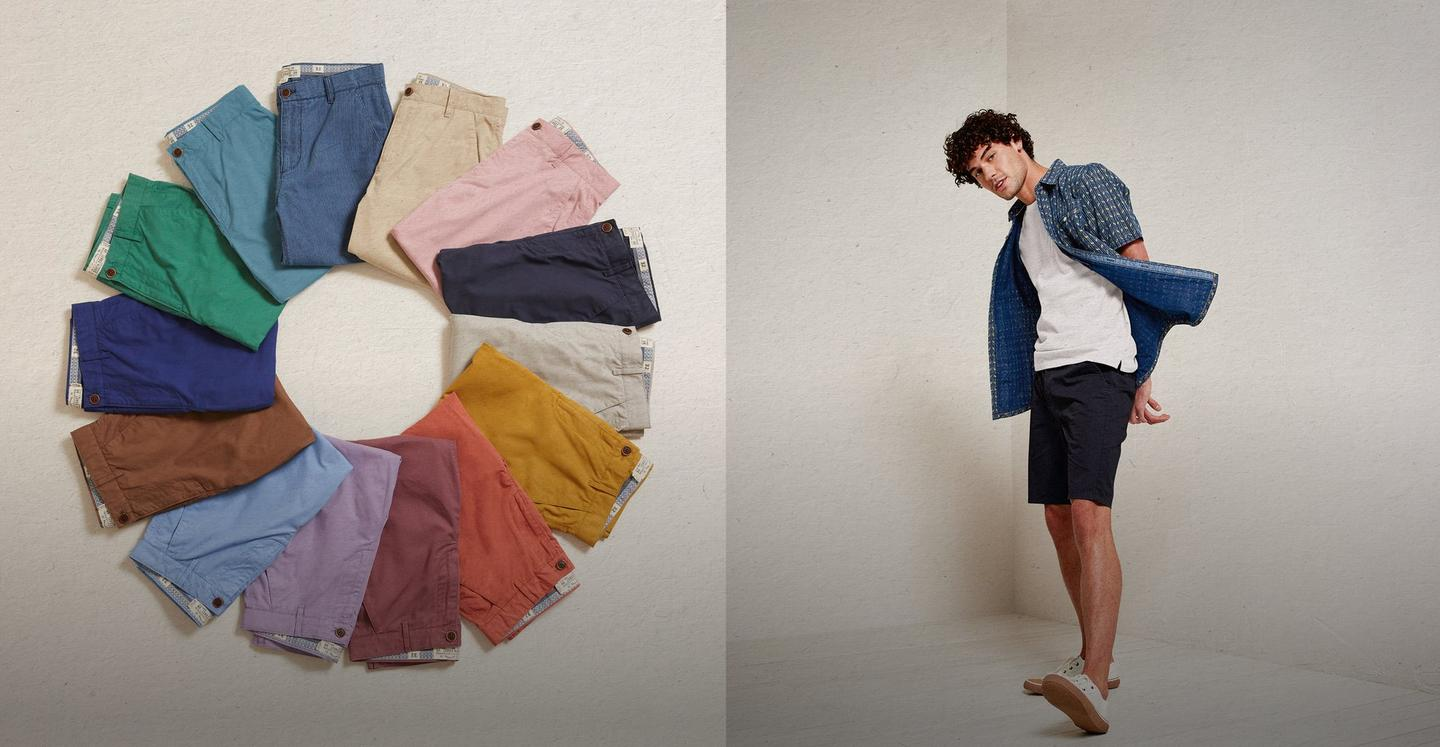 Men's chino shorts laid out in a colour wheel. Male model wearing a patterned blue shirt over a white T with navy chino shorts.