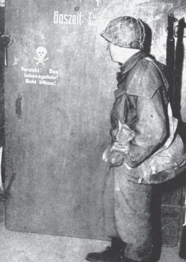 Alliierter Soldat nach Kriegsende vor einem Gaskammereingang im KZ.
