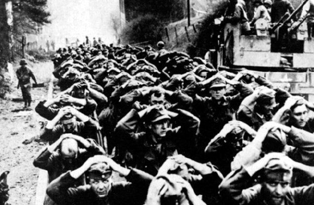 Soldaten der Deutschen Wehrmacht auf dem Weg in ein amerikanisches Kriegsgefangenenlager