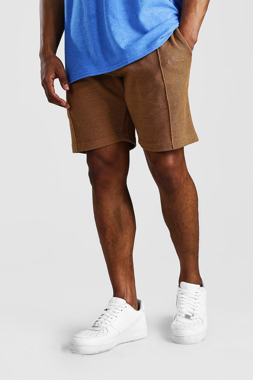 Фирменные шорты MAN средней длины из ткани пике с защипами фото