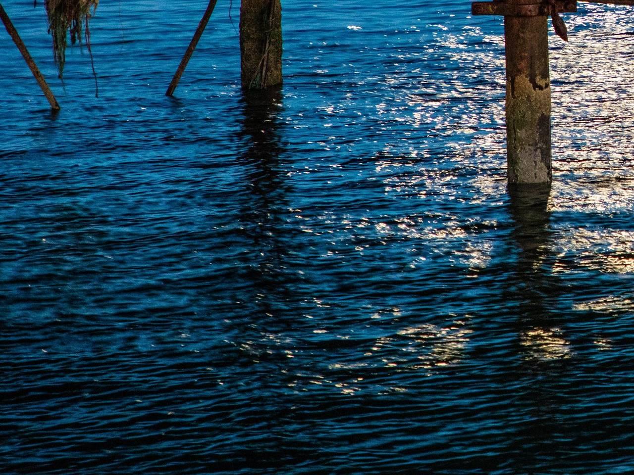 Dark blue sea by bridge structure