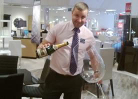 Man pouring wine into a huge wine glass