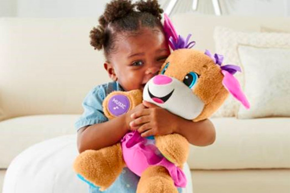 Little girl in living room setting cuddling Fisher-Price toy.