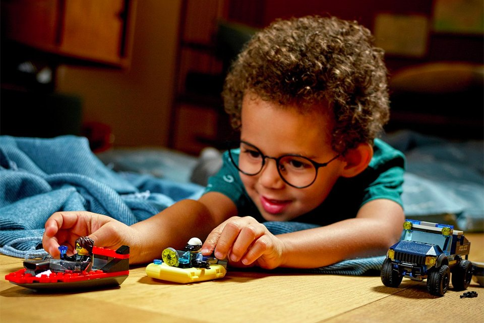 Little boy wearing glasses, lying on a blue blanket on the floor whilst playing with LEGO boats and cars.