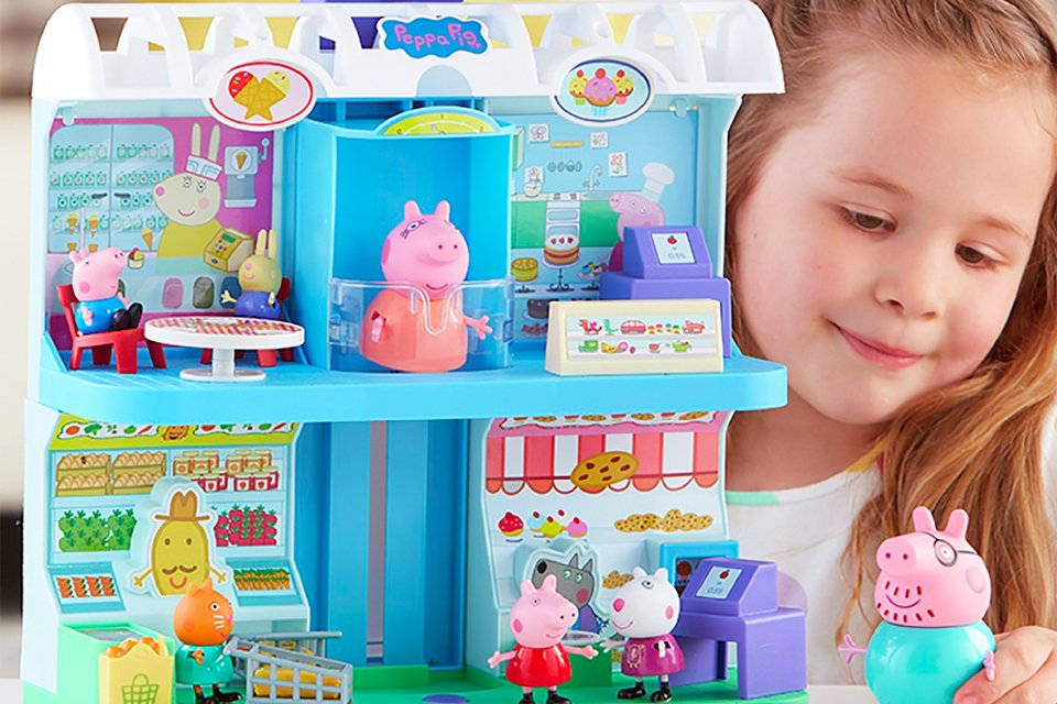 Little girl playing with Peppa Pig shooping centre playset.