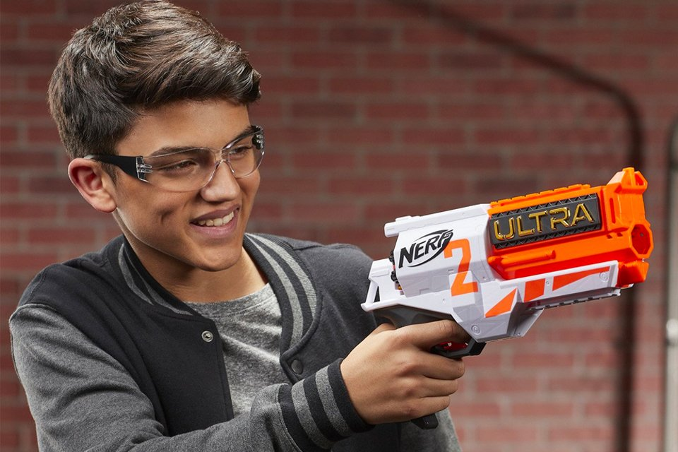 Smiling boy wearing protective glasses and pointing NERF gun with his right hand.
