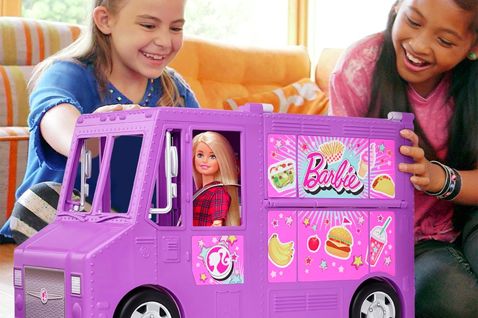 Two girls sat playing with purple Barbie food truck.