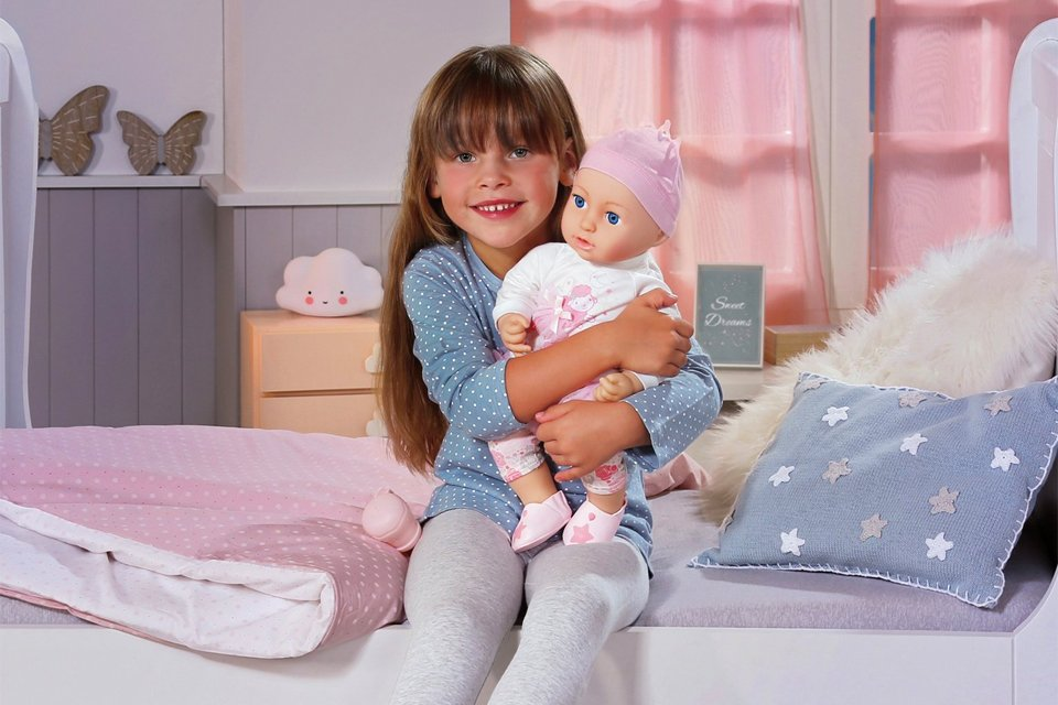 Girl sat on bed, smiling at the camera whilst hugging a Baby Annabell doll.