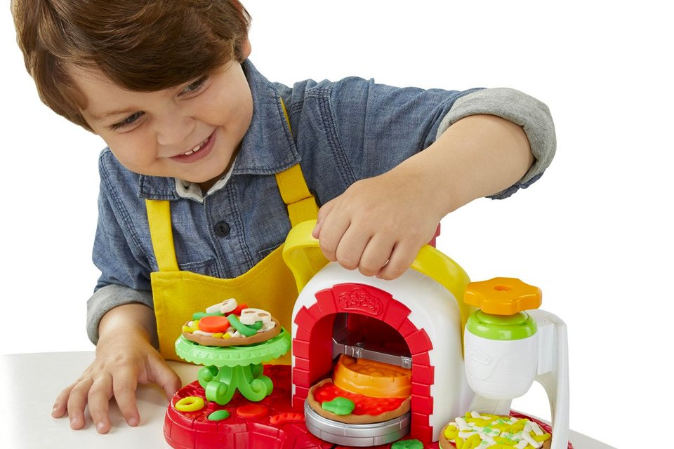 Little boy making Play Doh pizza with the Spin and Top Pizza set.