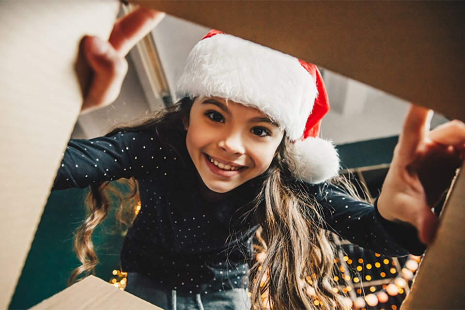 Image of girl wearing a santa hat and looking through a box into the camera.