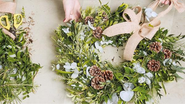 A home-made Christmas wreath decorated with pine cones and a hessian bow.