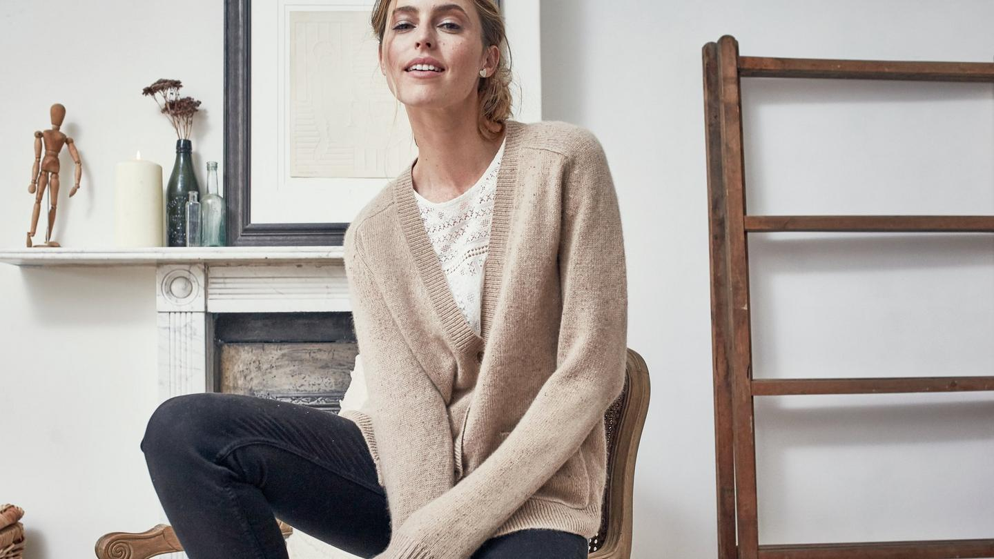 The Sophie Cardigan from FatFace with 5% cashmere, worn on a model sitting in a neutral colour living room