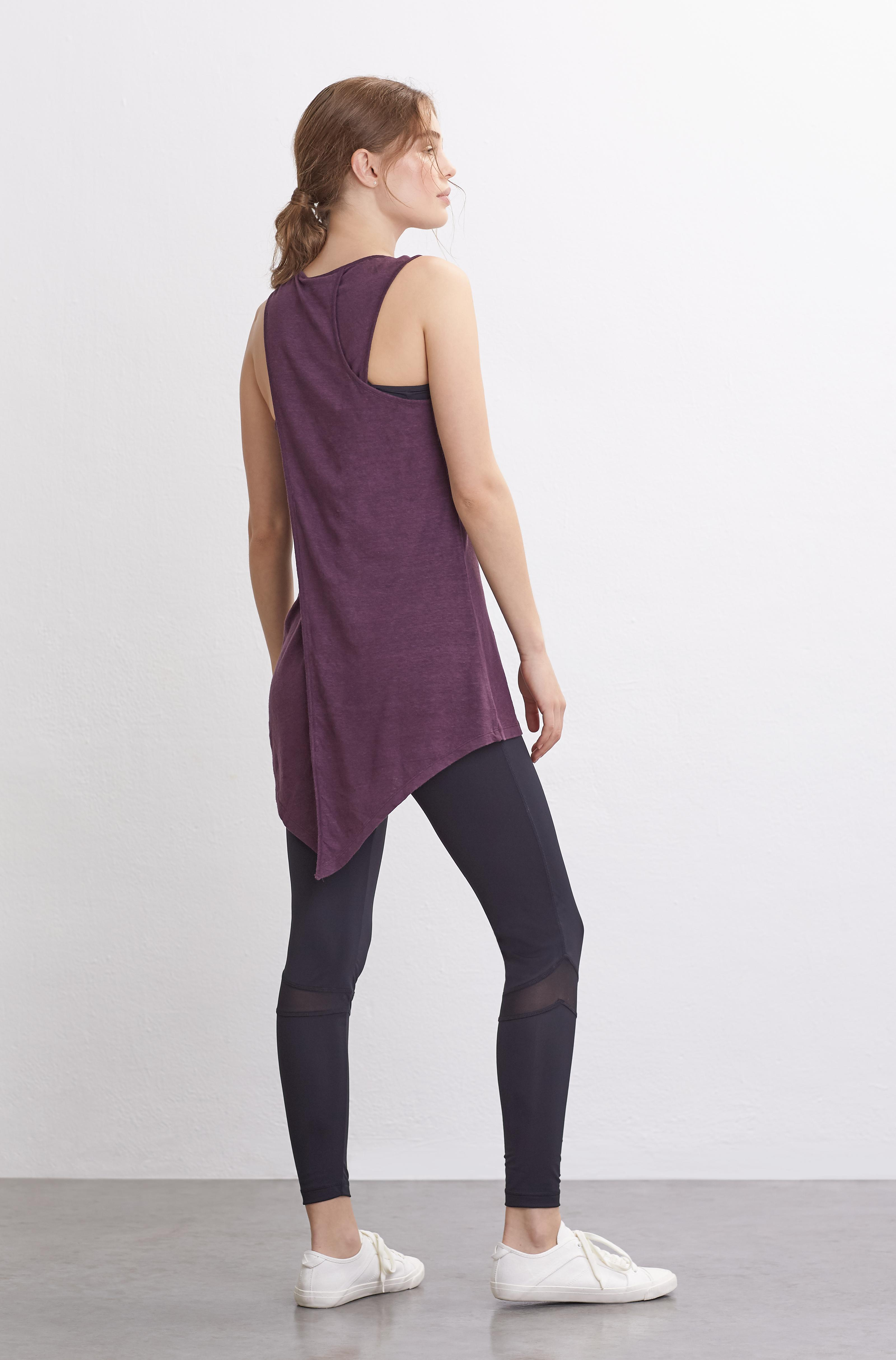 Female model with her back to the camera wearing a plum athleisure vest top with black gym leggings.