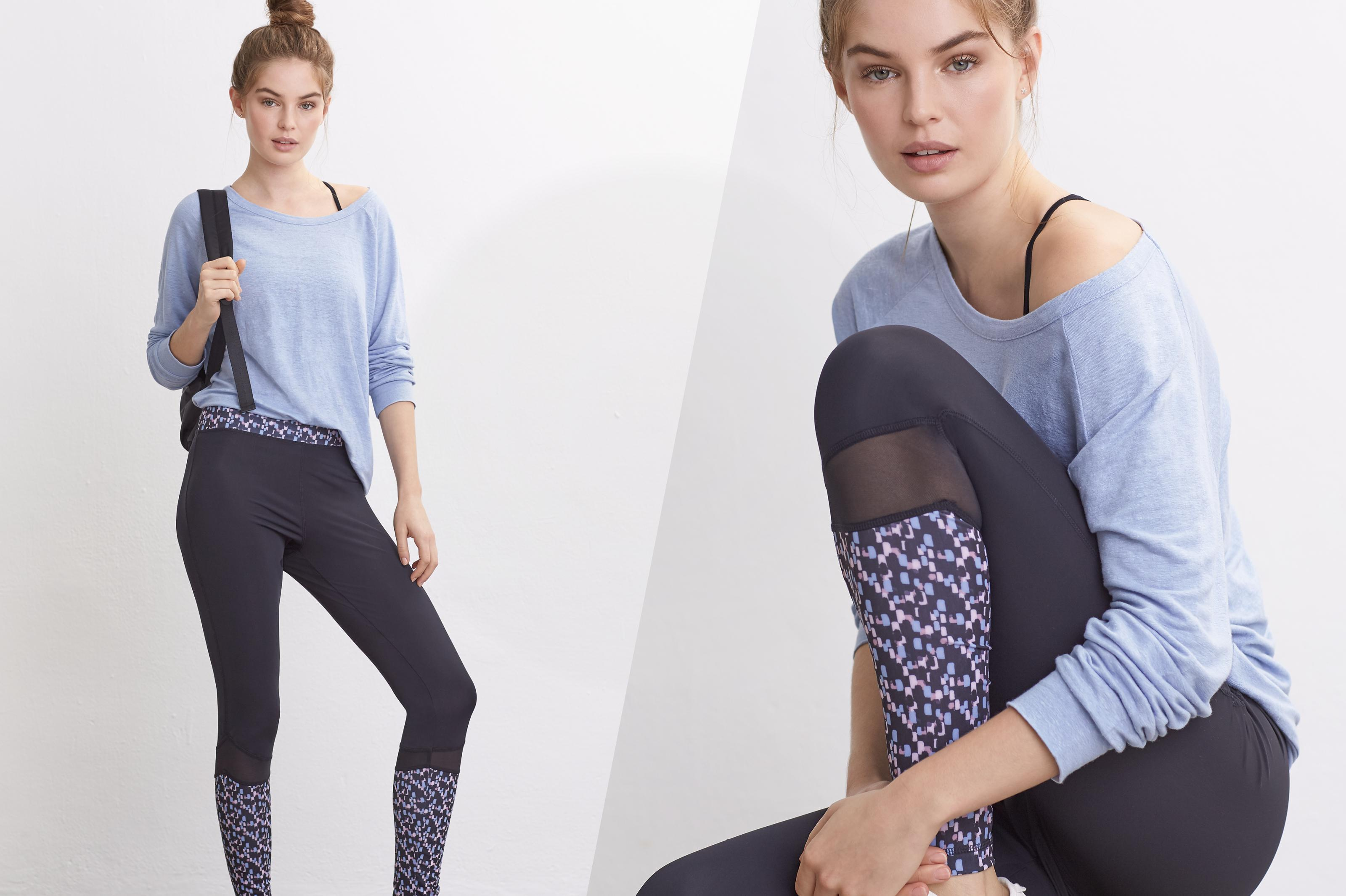 Two images of a female model wearing a light blue yoga top with black patterned gym leggings. One is of her standing and one sat down.