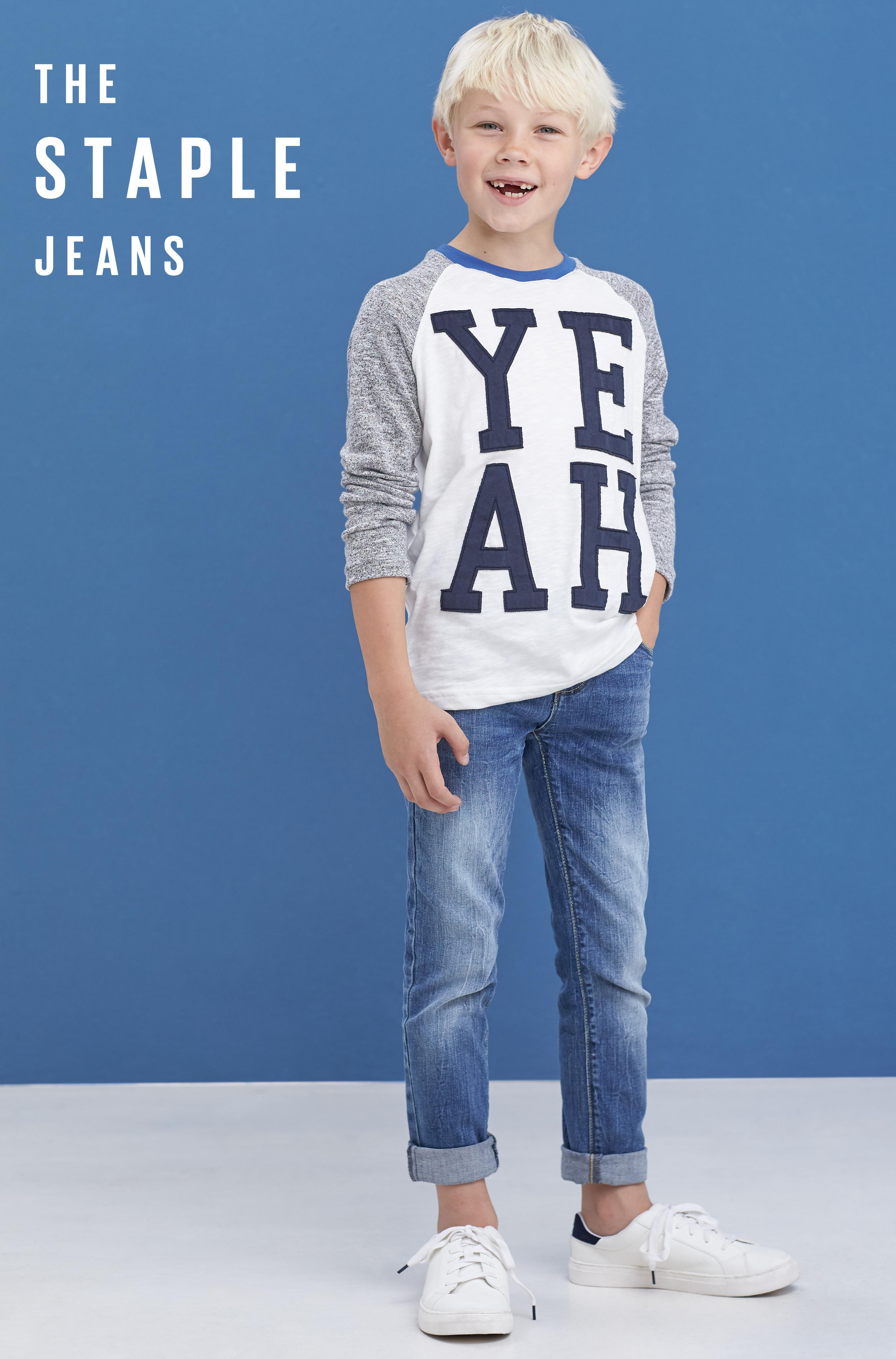 Boy model wearing a yeah graphic long sleeve t-shirt with mid wash denim jeans on a blue background.