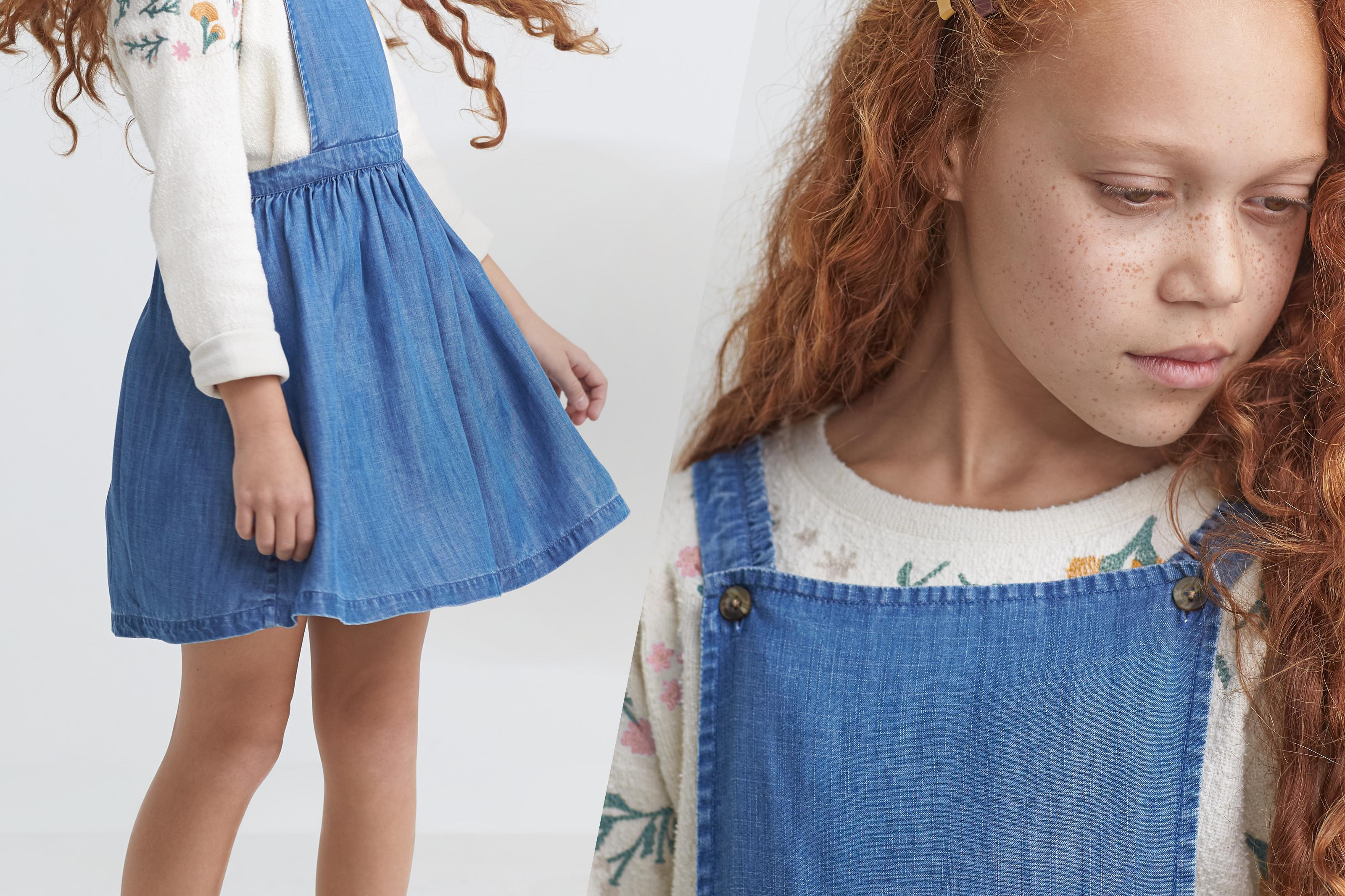 Two close up shots of a girl model wearing a denim pinafore dress with a floral embroidered ivory jumper.