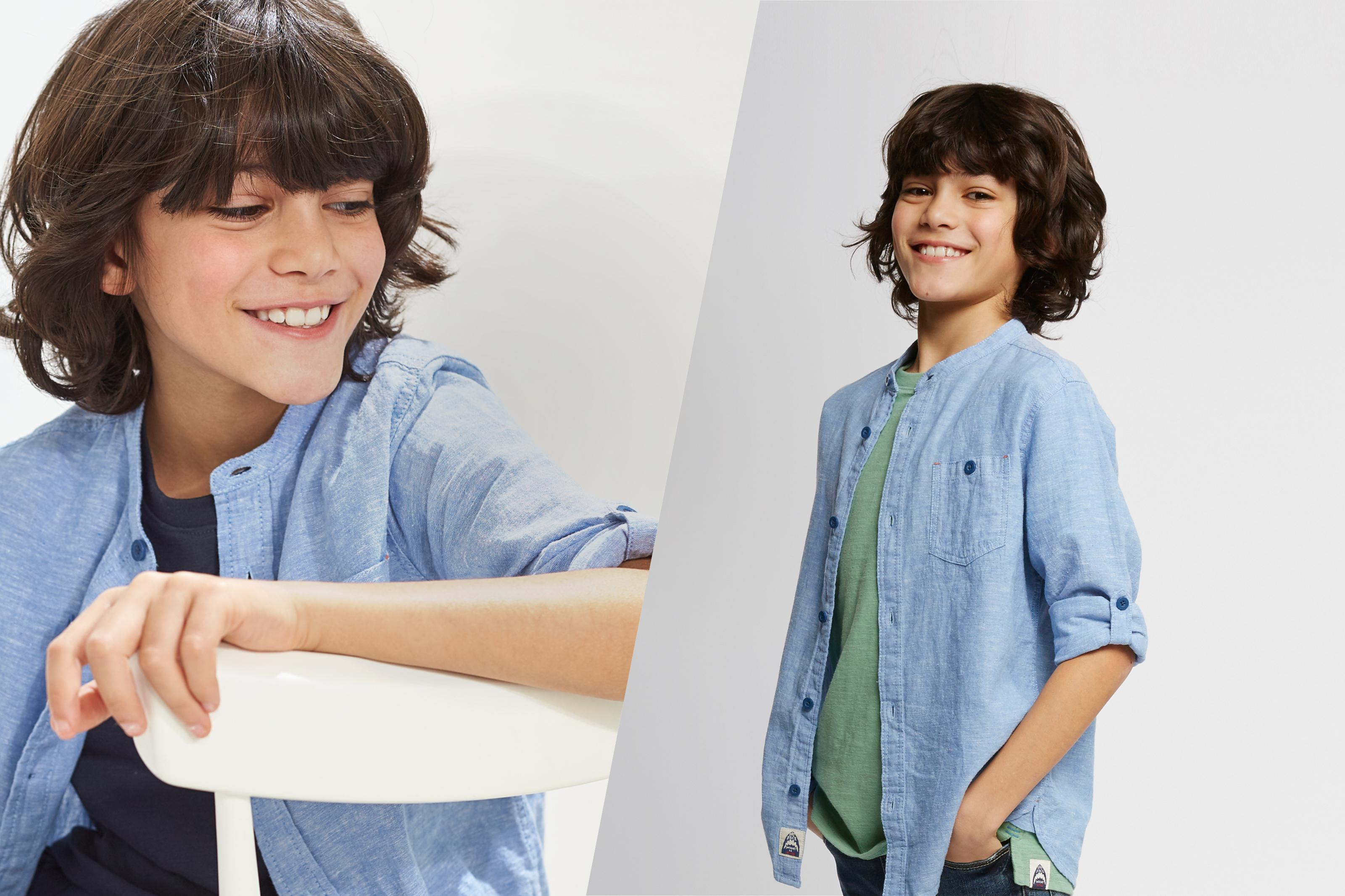 Boy wearing a chambray grandad collar shirt with patch pocket and button up cuffs.