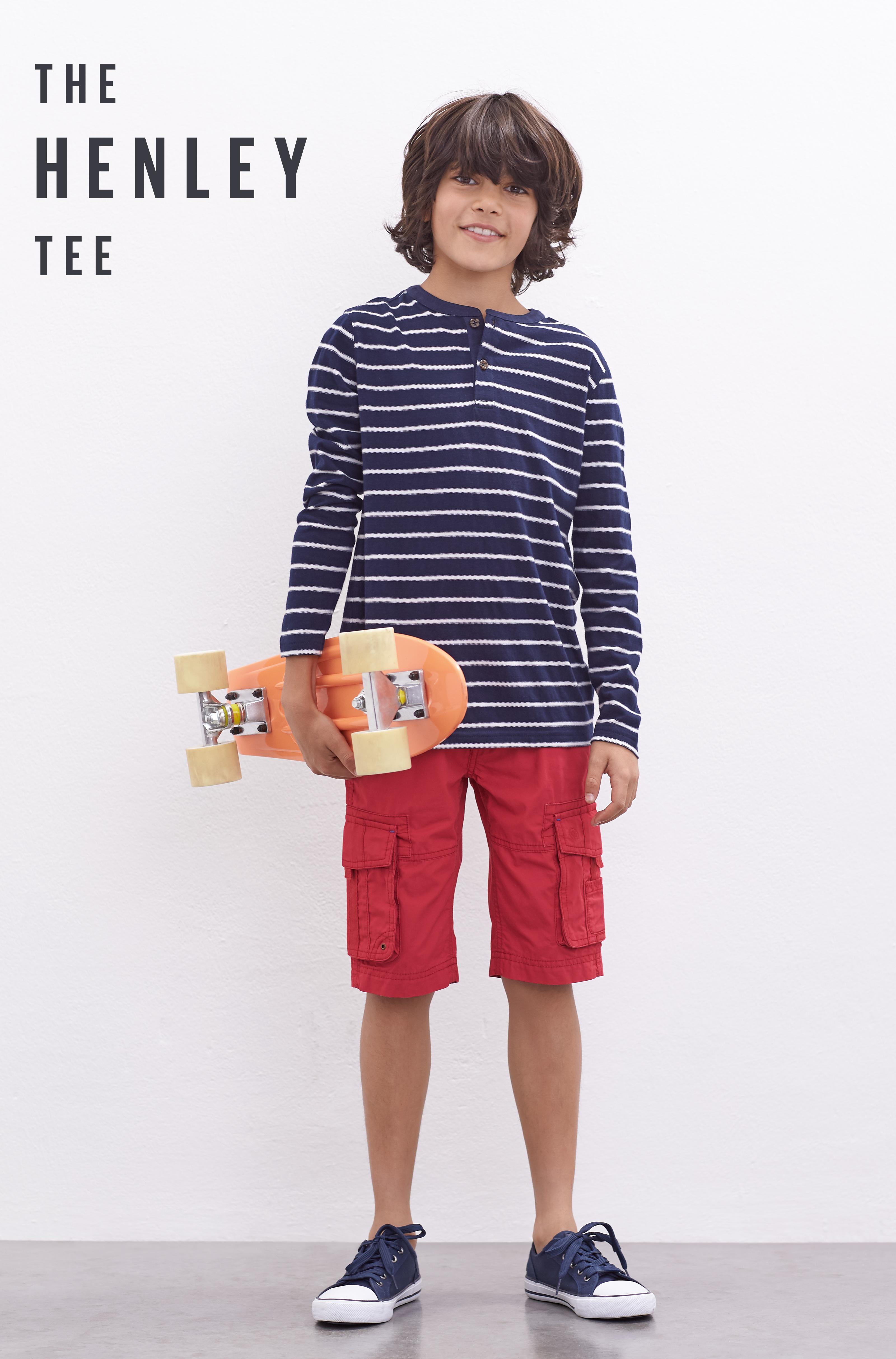 Boy model wearing a dark blue stripe button up top with red cargo shorts, holding a skateboard.