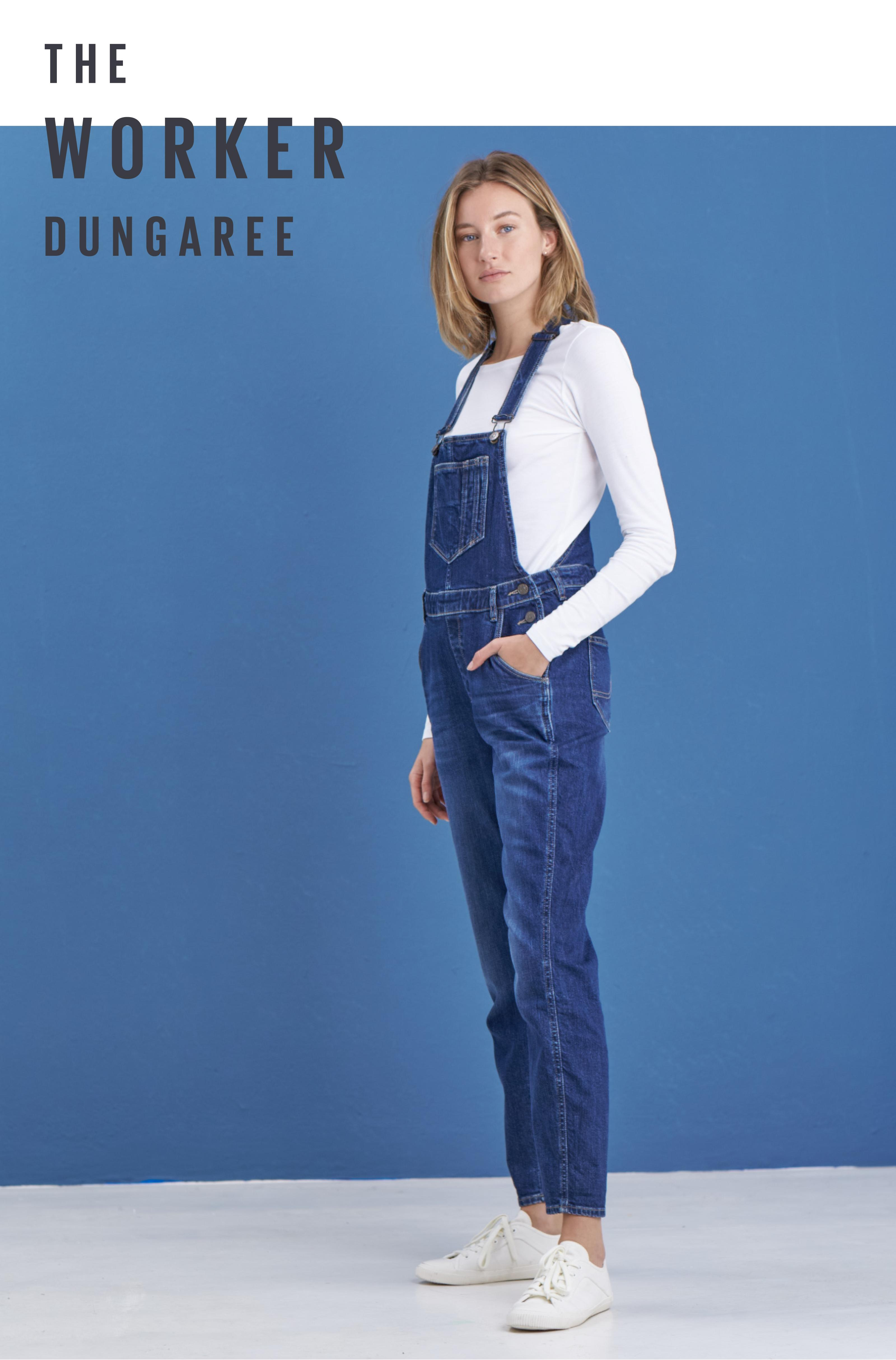 Female model wearing denim dungarees with a white long sleeve top and white trainers.