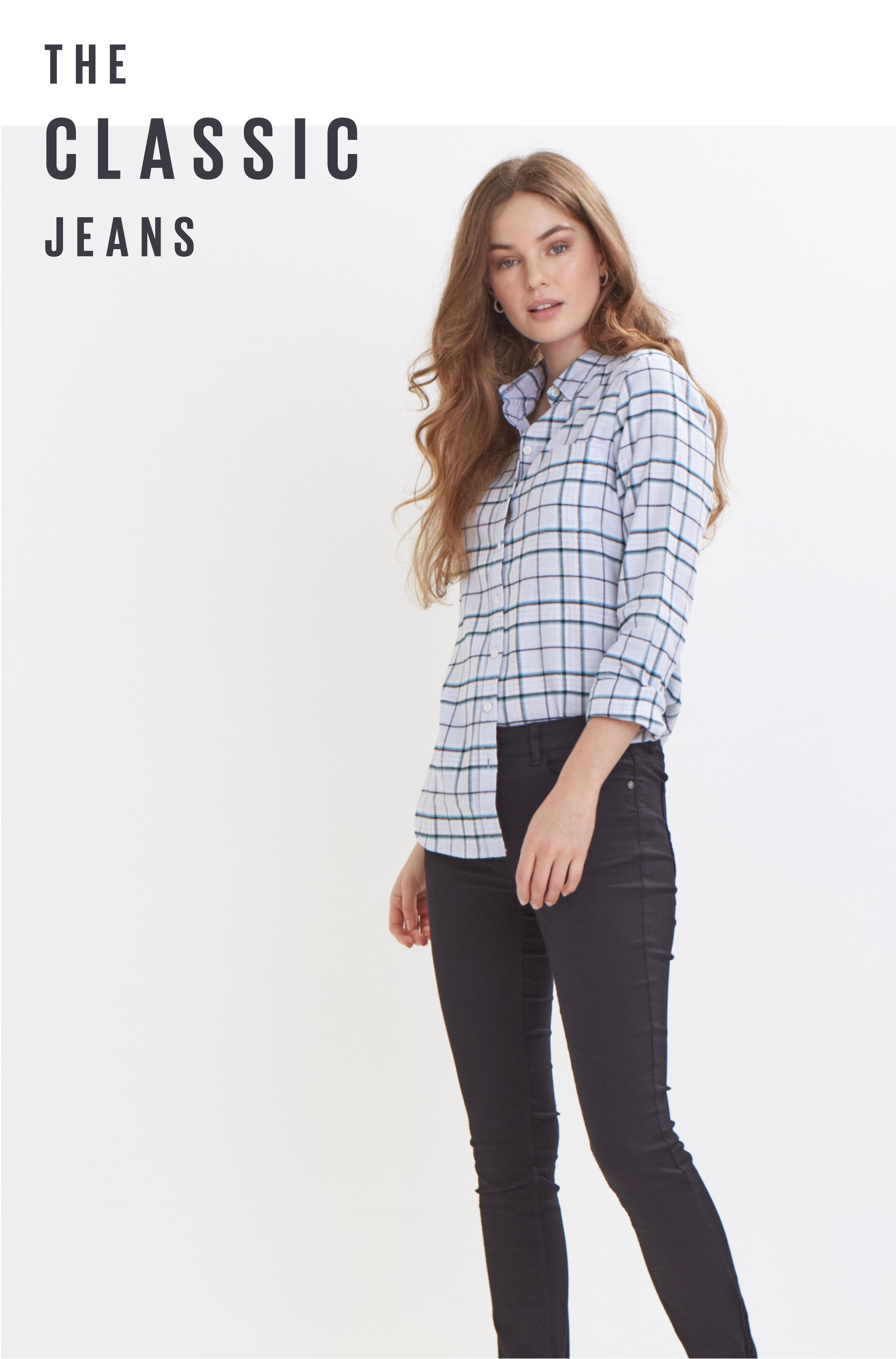 Female model wearing a light blue check shirt and black jeans.