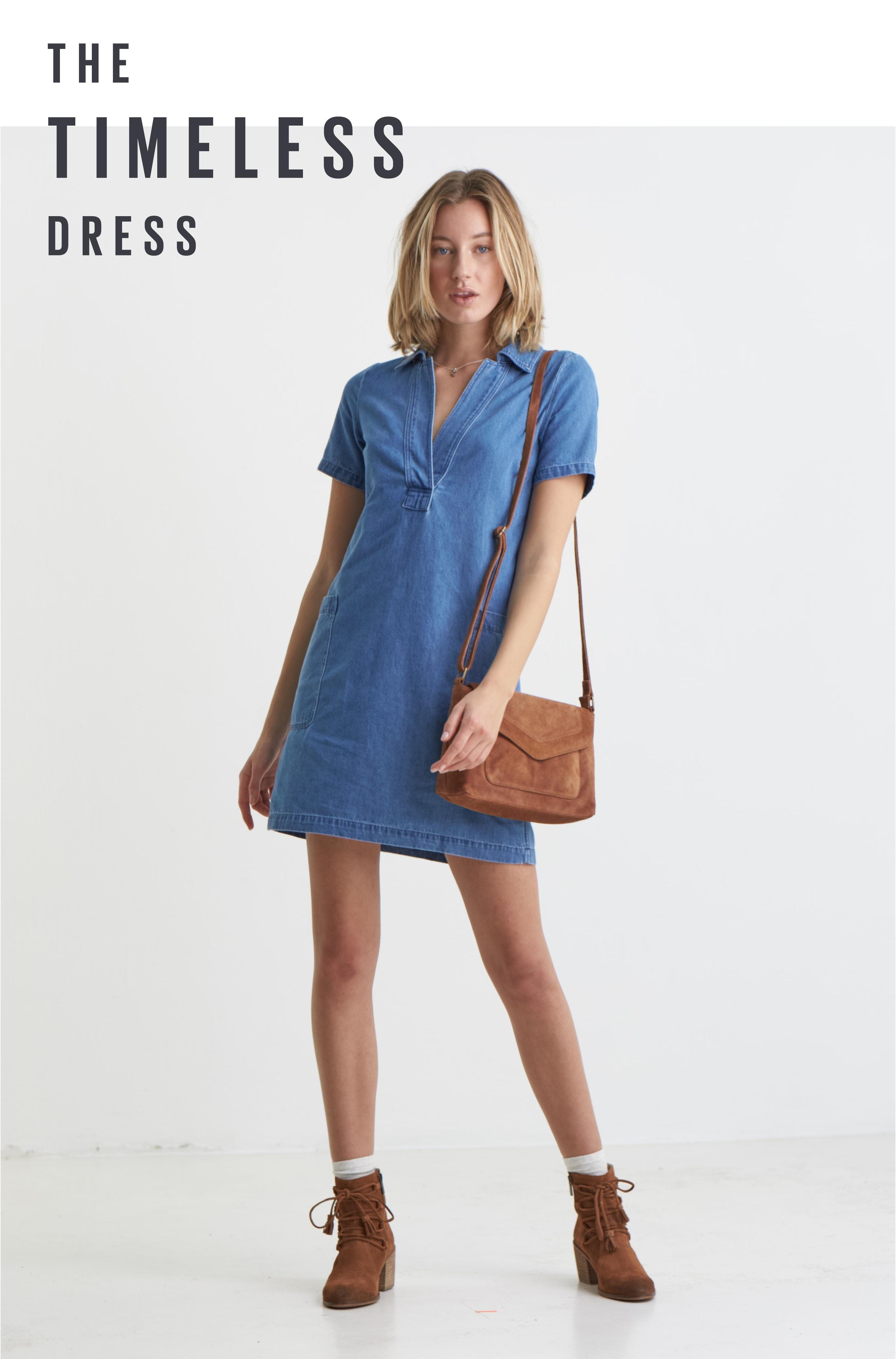 Female model wearing a denim blue dress with a brown leather bag and brown lace up boots.