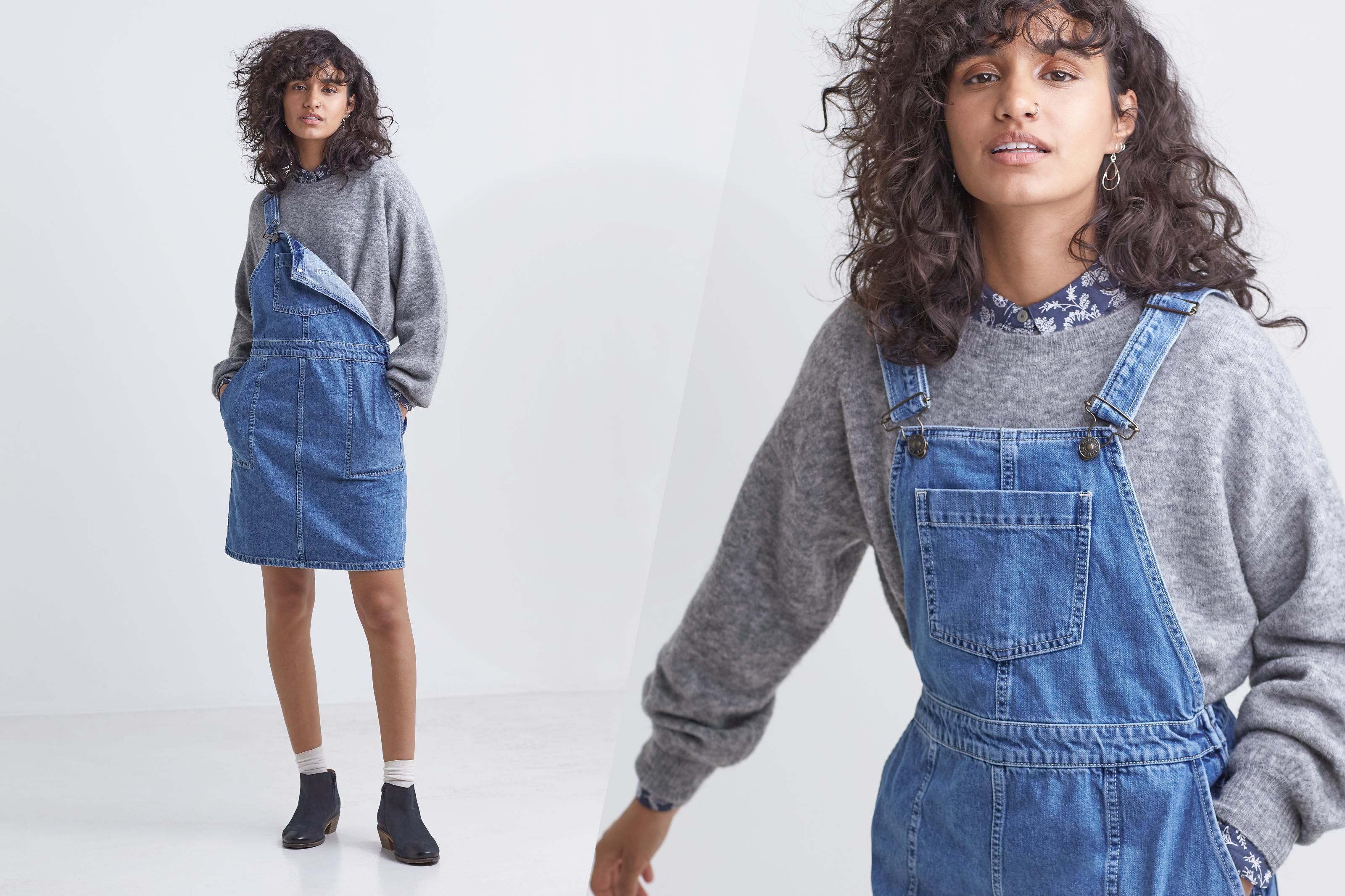 A female model wearing a denim dungaree mini dress with a grey wool jumper.