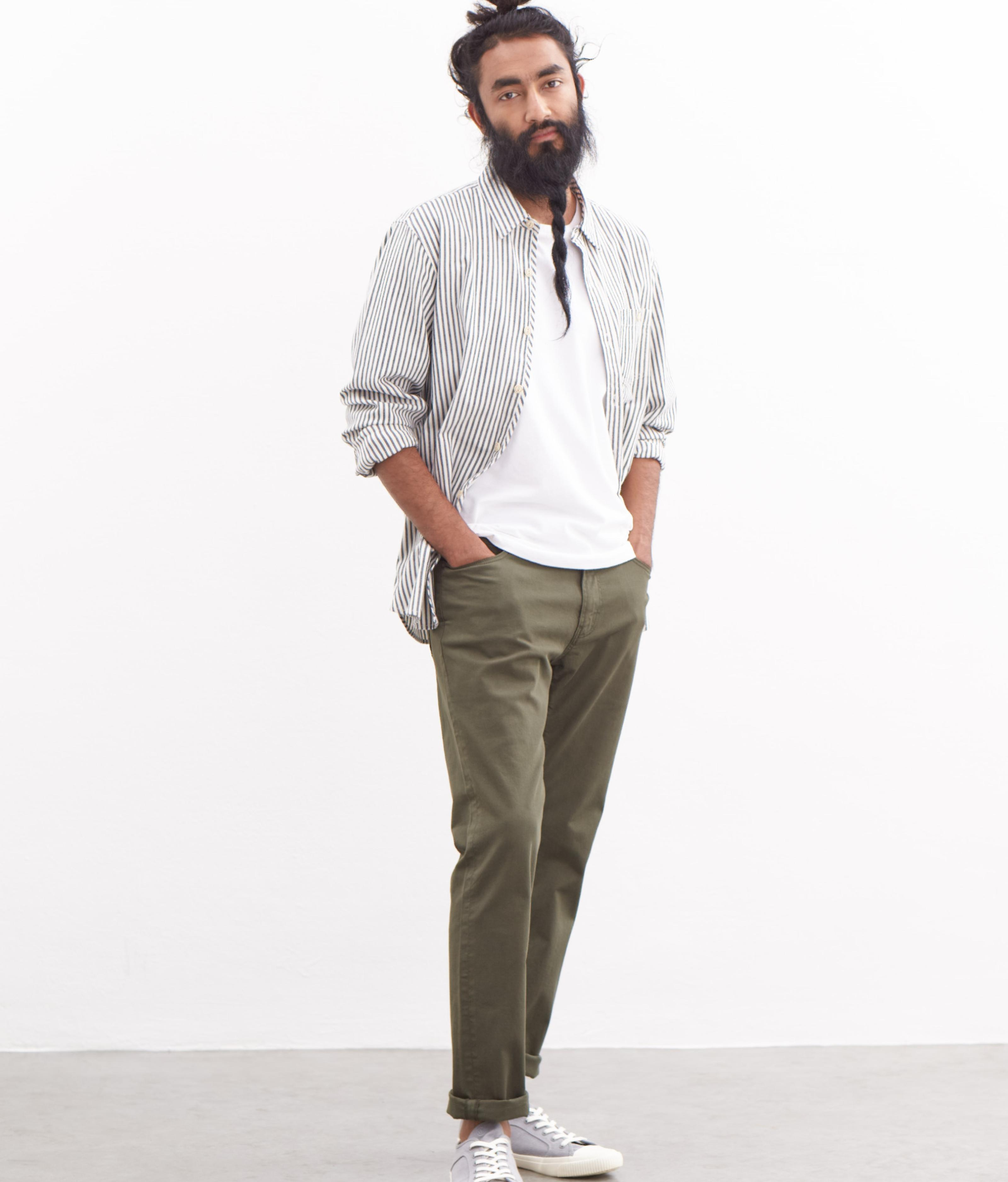 A male model wearing a grey stripe shirt and khaki trousers.