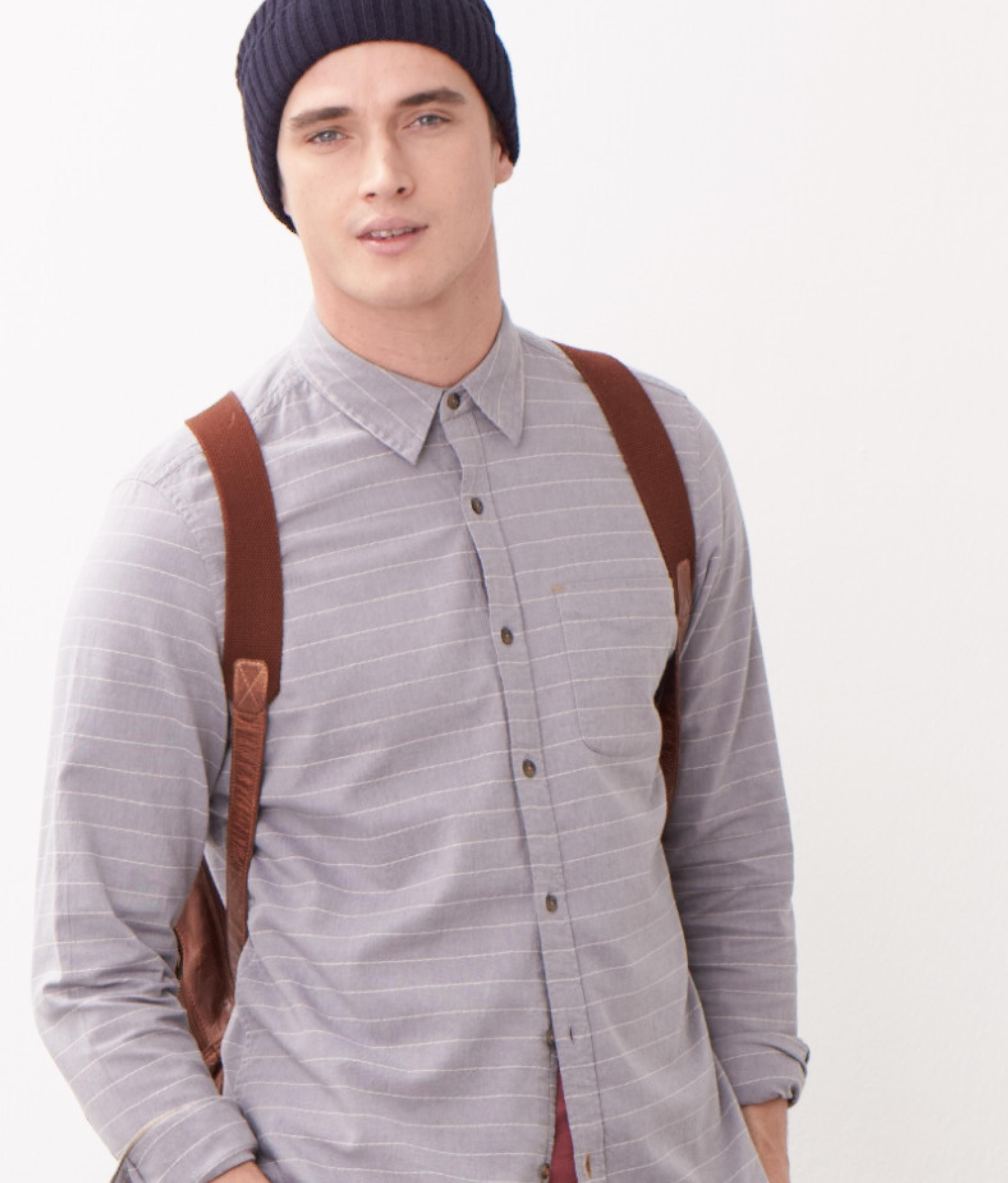 Close up of a male model wearing a grey shirt and a brown rucksack.