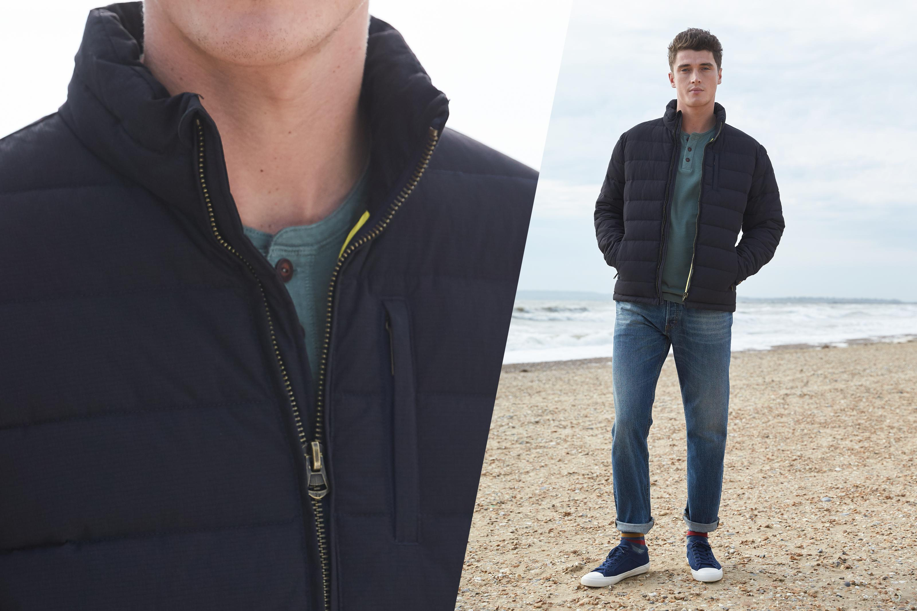 A male model wearing a blue puffer coat on the beach.