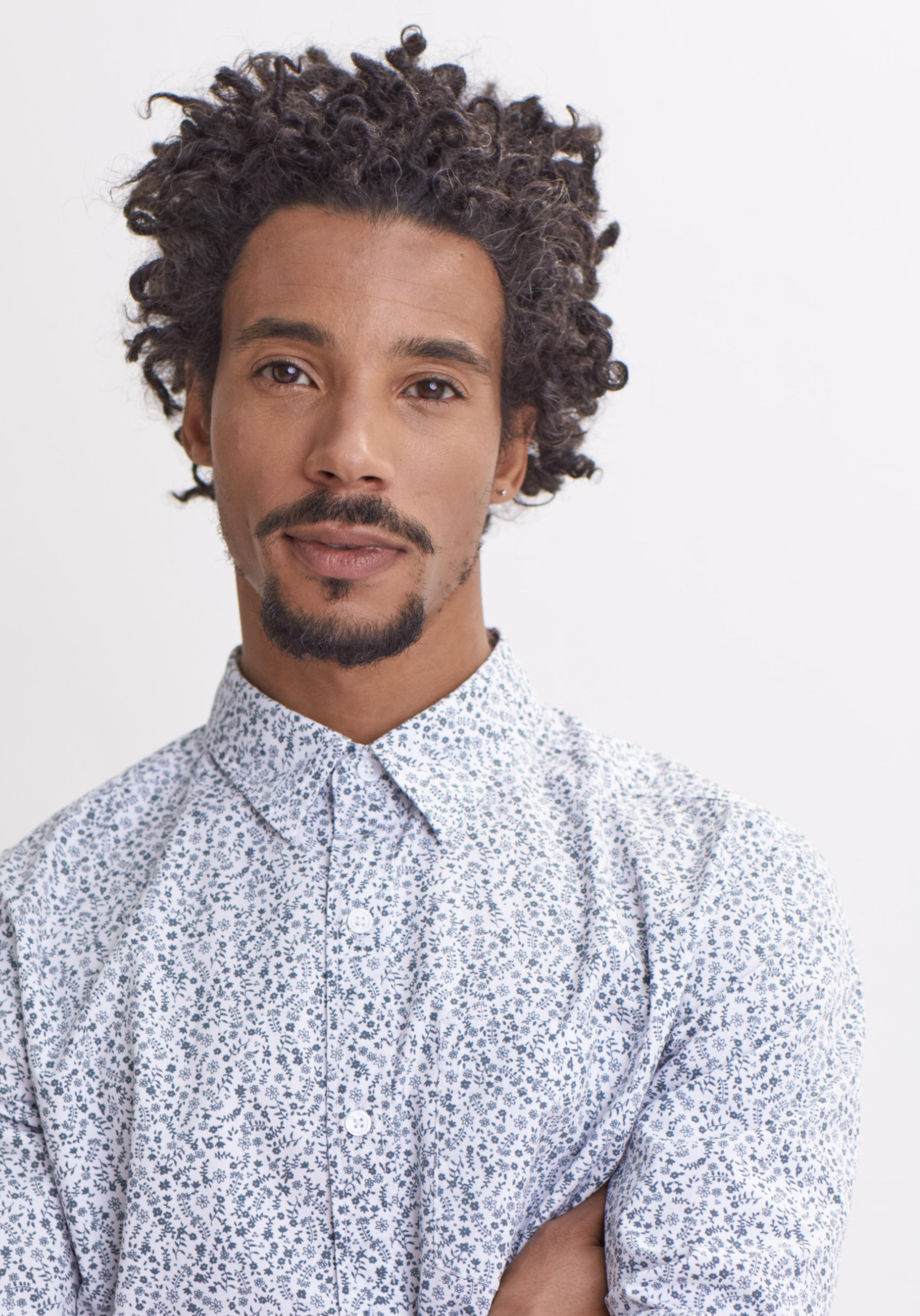 Male model wearing a white and blue floral shirt.