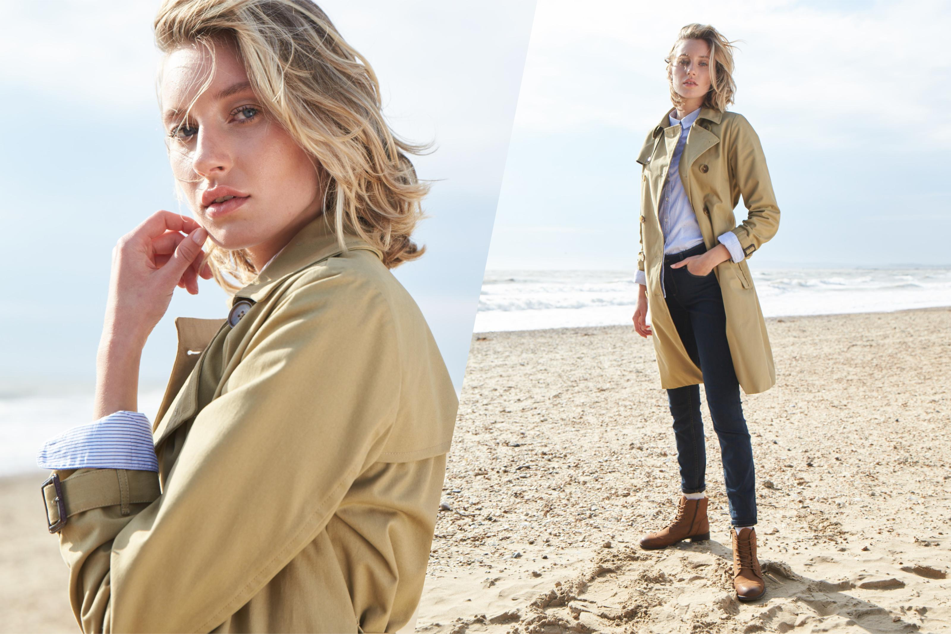 A female model wearing a camel trench coat on a pebbled beach.