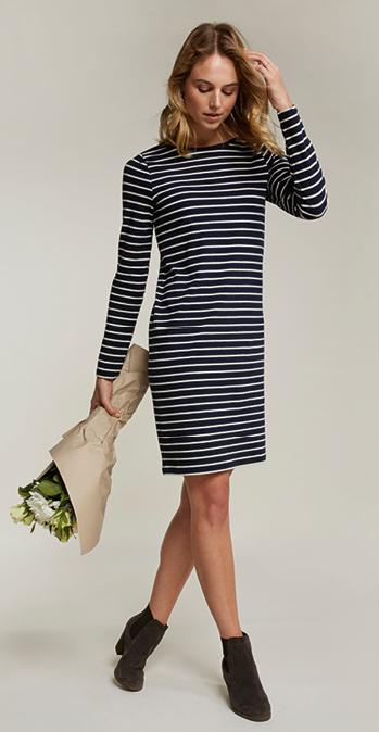 Female model holding a bouquet of flowers wearing the Aurelia Dress in navy.