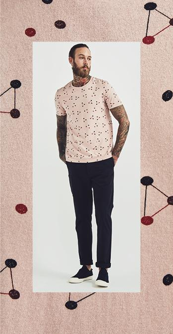 Male model wearing the pink Folk All Over Atom Graphic T-Shirt with the navy Folk Chino Trousers and the navy Organic Cotton Lace Up Trainers