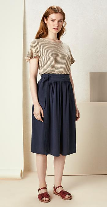 Female model wearing the Everly Sparkle Linen Tee and the Adele Tencel Midi Skirt on a cream background