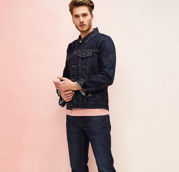 A male model wears double denim with a pink tee poking out