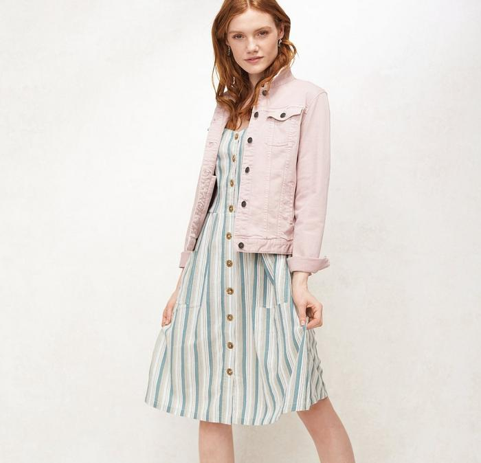 A pink denim jacket worn with a green stripe dress from FatFace, worn by a red-haired model