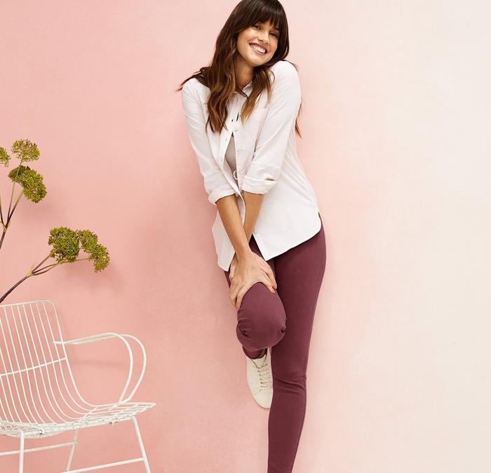 A brown-haired model wears a FatFace pink stripe tee and bright pink leggings