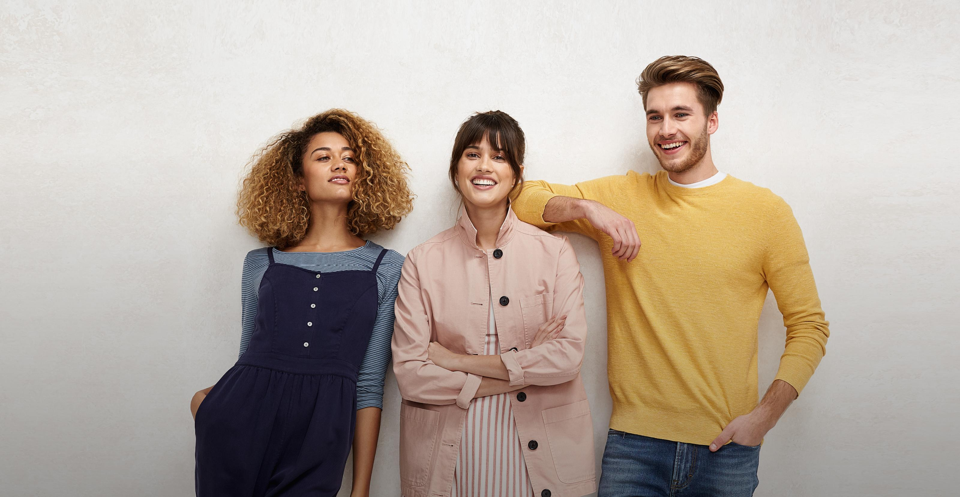 Two female models wearing a blue dress and pink jacket and one male model wearing a yellow jumper