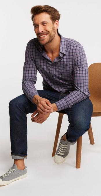Male model sat on stool wearing the Ballast Check Shirt in grey with denim jeans and the grey organic cotton lace up trainers