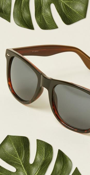 The tortoiseshell Classic Vintage Sunglasses with green leaves surrounding it