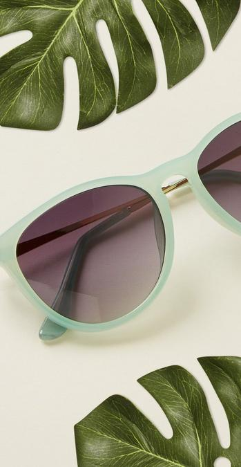 Close up detail shot of the Emma Sunglasses in green with some green leaves