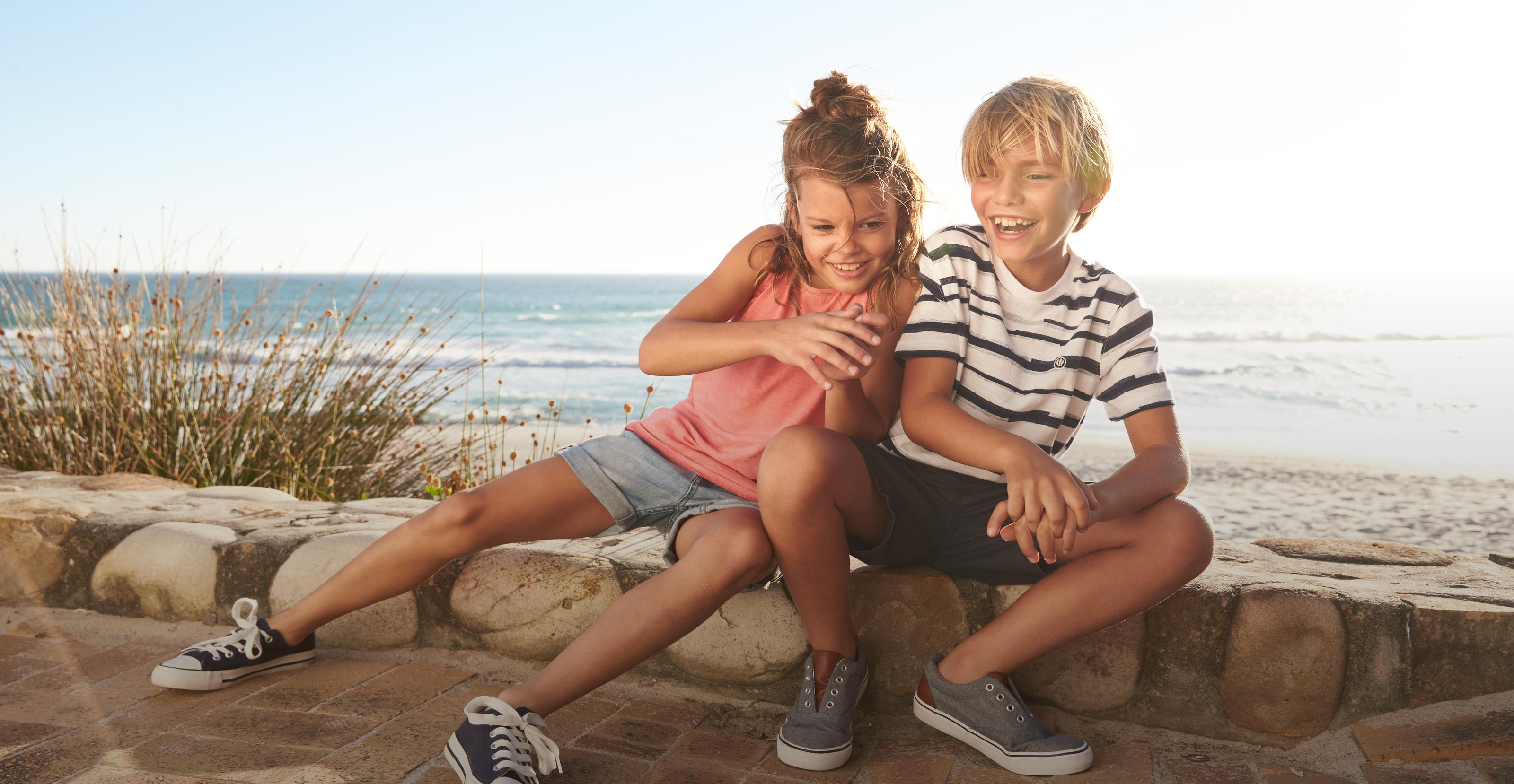 Image of a girl and boy model. The girl is wearing a pink top with blue shorts and the boy is wear a white and blue stripe tee with shorts