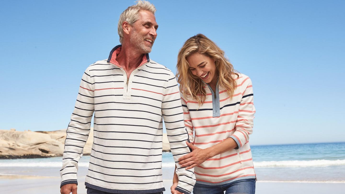 A man and a woman wearing striped Airlie Sweatshirts, holding hands on the beach.