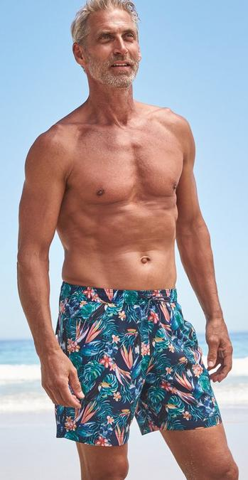 Male FatFace model standing on a beach wearing Tropical Print Camber Swim Shorts