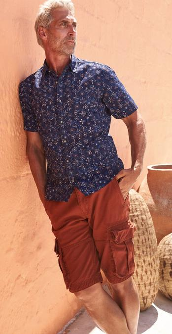 Male FatFace model wearing a navy Batik Print short sleeve shirt and chestnut red Breakyard Cargo Shorts