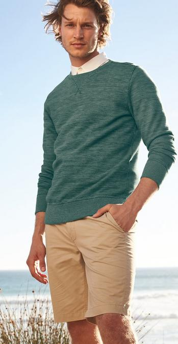 Male FatFace model wearing beige Cove Flat Front Shorts and a green sweatshirt.