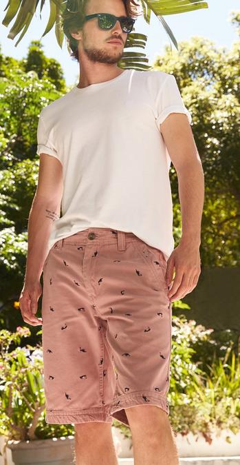 Male FatFace model standing in a garden wearing a plain white t-shirt and pink Palm Tree Embroidered Shorts.