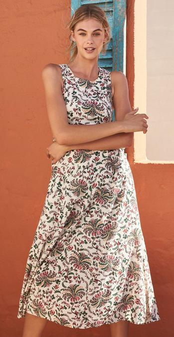 Female FatFace model wearing Alhambra Print Connie Dress against a terracotta background.
